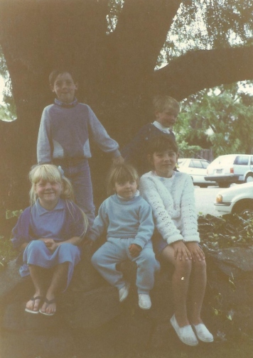 My brothers and sisters (minus one) and I sitting on a tree. I'm the little one in the middle with the blue track suit.